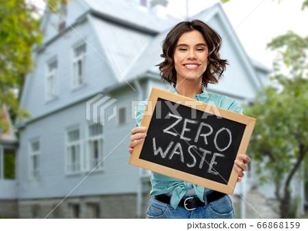 happy woman with chalkboard with zero waste words 66868159