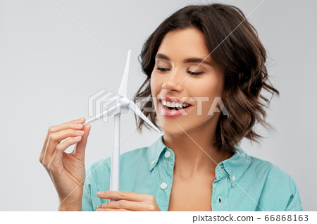 happy smiling young woman with toy wind turbine 66868163