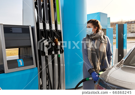 woman in mask filling car at gas station 66868245