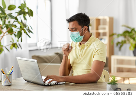 sick indian man in mask with laptop works at home 66868282