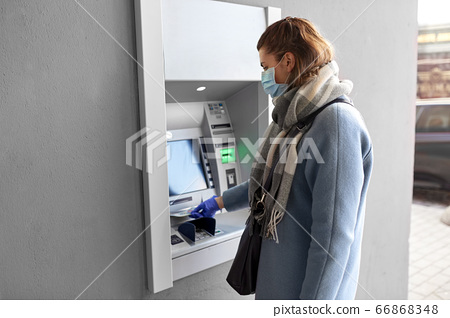 hand in medical glove with money at atm machine 66868348