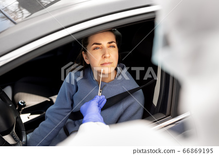 healthcare worker making coronavirus test at car 66869195