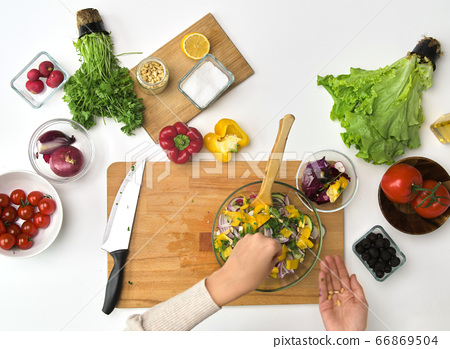 hands cooking vegetable salad on kitchen table 66869504