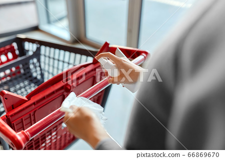 woman cleaning shopping cart handle with sanitizer 66869670