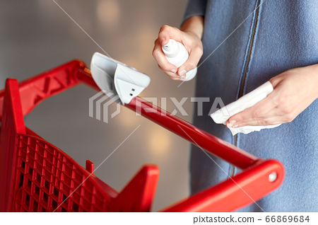 woman cleaning shopping cart handle with sanitizer 66869684