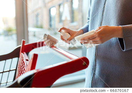 woman cleaning shopping cart handle with sanitizer 66870167