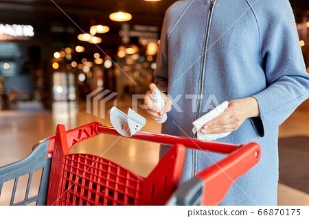 woman cleaning shopping cart handle with sanitizer 66870175
