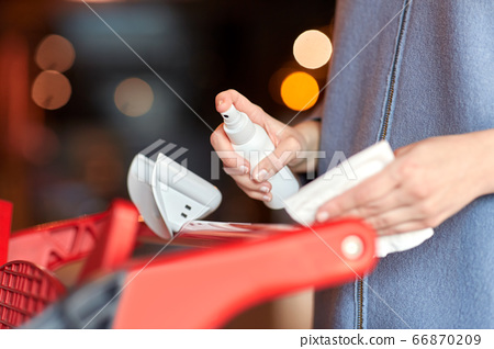 woman cleaning shopping cart handle with sanitizer 66870209