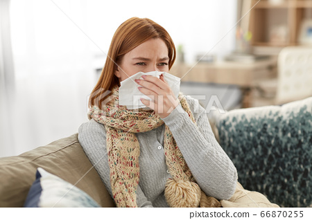 sick woman blowing nose in paper tissue at home 66870255
