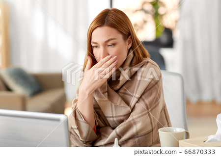 sick woman having video call on laptop at home 66870333