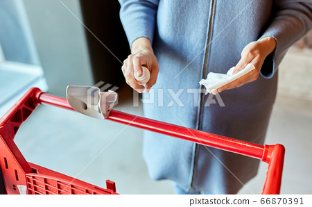 woman cleaning shopping cart handle with sanitizer 66870391