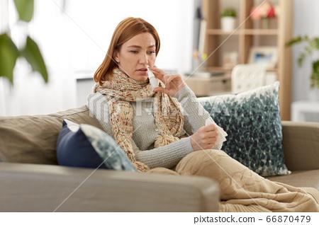 sick woman using nasal spray at home 66870479