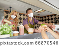 sellers in masks serving customers at food truck 66870546