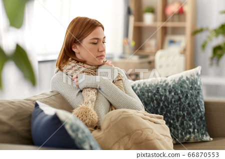 sad sick woman in blanket and scarf at home 66870553