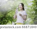 在運動服的少婦飲用水以新鮮的綠色 66871840