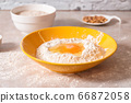 baking ingredients, flour, salt, eggs and oil in white and yellow bowls on marble countertop in bright homey kitchen 66872058