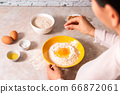 homemade bread baking. closeup woman hands adding salt in flour, dough preparation in bright kitchen with marble countertop 66872061