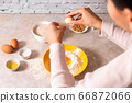 homemade bread baking. closeup woman hands adding egg in flour, dough preparation in bright kitchen with marble countertop 66872066