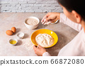 homemade bread baking. closeup woman hands mixing ingredients for dough preparation in bright kitchen with marble countertop 66872080
