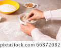 homemade bread baking. closeup woman hands mixing ingredients for dough preparation in bright kitchen with marble countertop 66872082