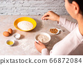 homemade bread baking. closeup woman hands mixing ingredients for dough preparation in bright kitchen with marble countertop 66872084