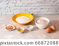 baking ingredients, flour, salt, eggs and oil in white and yellow bowls on marble countertop in bright homey kitchen 66872088