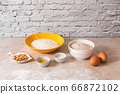 baking ingredients, flour, salt, eggs and oil in white and yellow bowls on marble countertop in bright homey kitchen 66872102