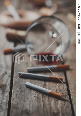 Cigarette and wine on the wooden table 66874507