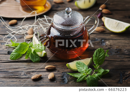 Hot black tea with lemon and mint on the wooden 66876223