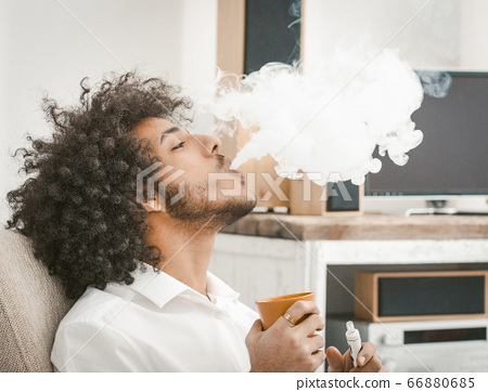Profile view of shaggy man smoking of e-cigarette and drinking coffee. Copy space in white smoke cloud. Close up shot. Tinted image 66880685