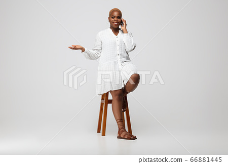 Young african-american woman in casual wear on gray background. Bodypositive female character, plus size businesswoman 66881445