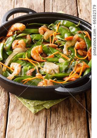 Tasty fried shrimp with onions, carrots and pea 66882579