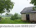 Heavy rain near an old abandoned house in a 66891637