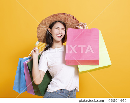 young woman in summer hat and holding shopping 66894442