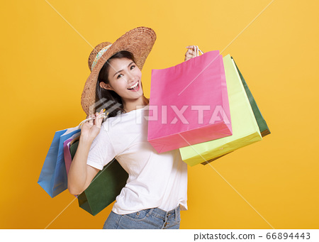 young woman in summer hat and holding shopping 66894443