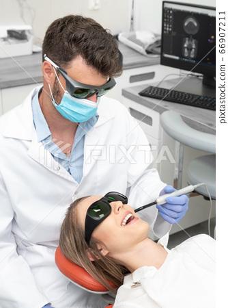 Using a modern method of laser teeth treatment 66907211