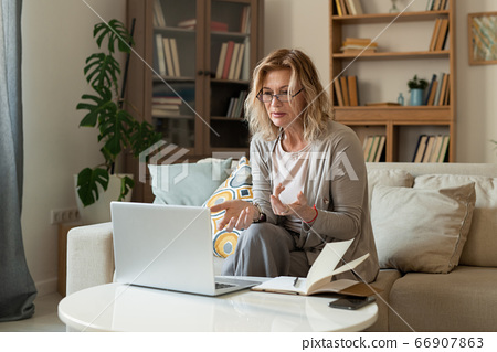 Middle aged female explaining something to online interlocutor during talk 66907863