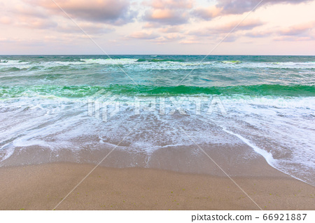 cloudy sunset sea side. waves running the sandy 66921887