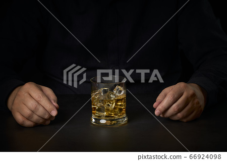 close-up of a man's hands with a glass of Scotch 66924098