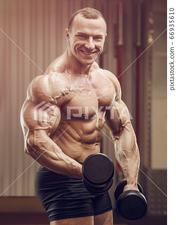 Bodybuilder strong man pumping up biceps muscles 66935610