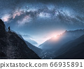 Arched Milky Way, woman and mountains at night. Silhouette of standing girl on the mountain peak 66935891