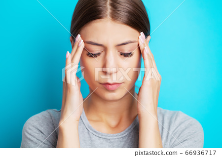 Head pain, exhausted young woman has suffering from unbearable headache 66936717