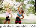 Sporty young woman doing stretching at public park in the morning,Couple friends girl warming up outdoor 66938558