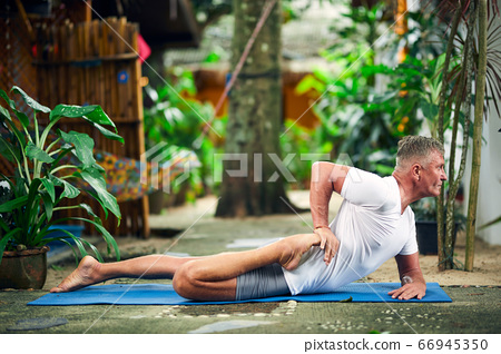 Man practice yoga in the tropical garden 66945350