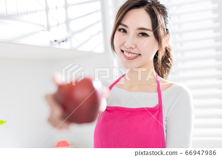 Asian housewife hold an apple 66947986