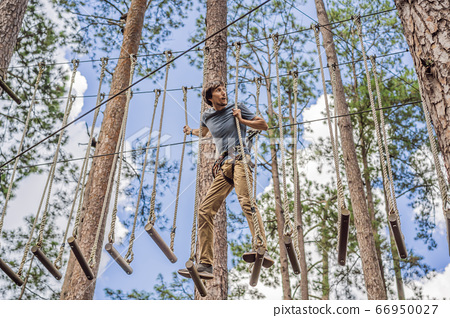 Young attractive man in adventure rope park in safety equipment 66950027