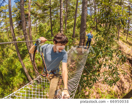 Young attractive man and woman in adventure rope park in safety equipment 66950038