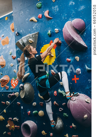 Young woman climbing a tall, indoor, man-made rock climbing wall 66952058