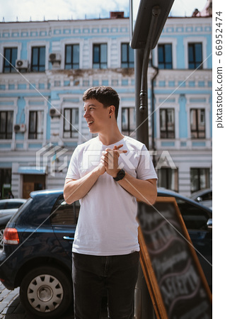 Man in gray t-shirt and jeans over city street background 66952474