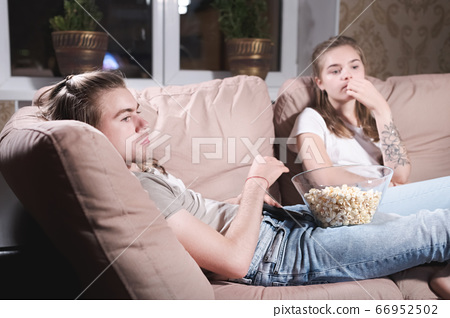 a loving young couple stupid misunderstanding on the couch at the telefizor watching a movie or news. Neutral positive emotions in the hug of a young family. The concept of leisure at home. 66952502